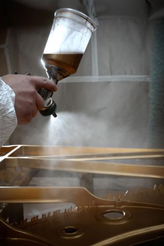 Hand mit Lackierpistole und Becher beim Lackieren einer Steinway & Sons Gussplatte