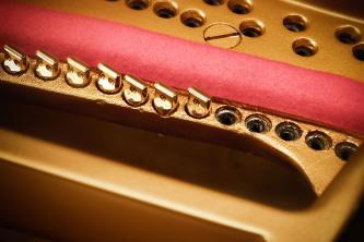 Steinway-Gussplatte mit rotem Filz und Agraffen