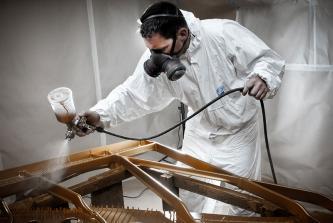 Uwe Weschenfelder mit Lackierpistole, Lackieranzug, Maske beim Lackieren einer Steinway & Sons Gussplatte