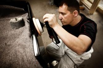 Uwe Weschenfelder beim Polieren eines Steinway-Flügels, in der Hand eine Poliermaschine